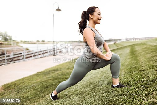 istock fitness woman stretching in the grass 913630170