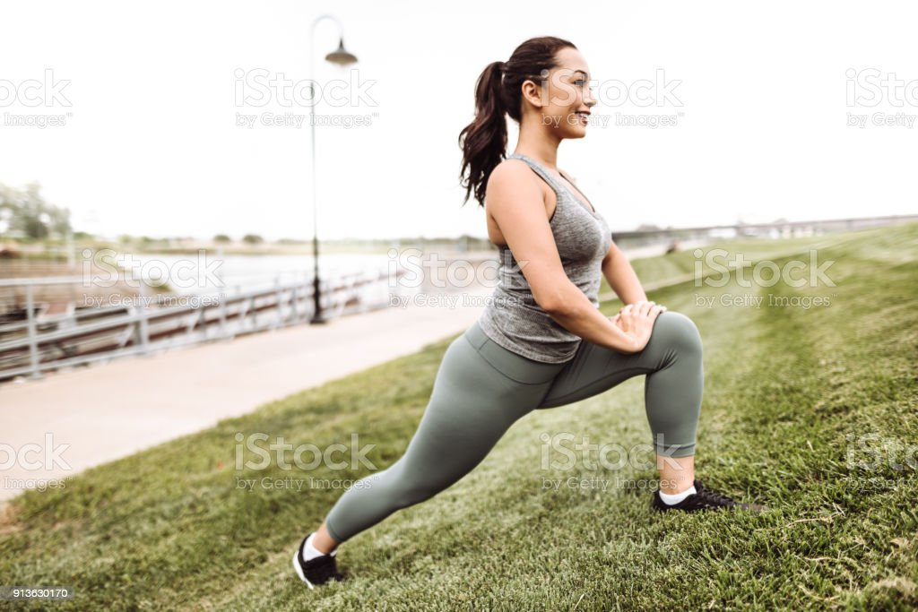 fitness woman stretching in the grass stock photo