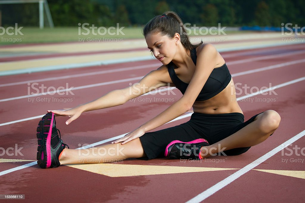 Fitness Woman Stretching on a Track with Blurred Background stock photo