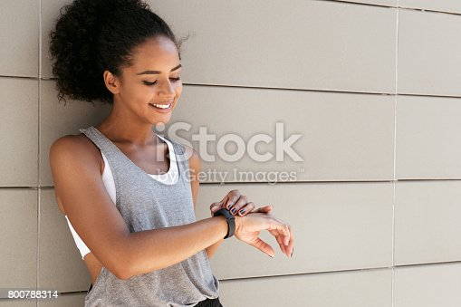Fitness woman taking a break, checking activity tracker