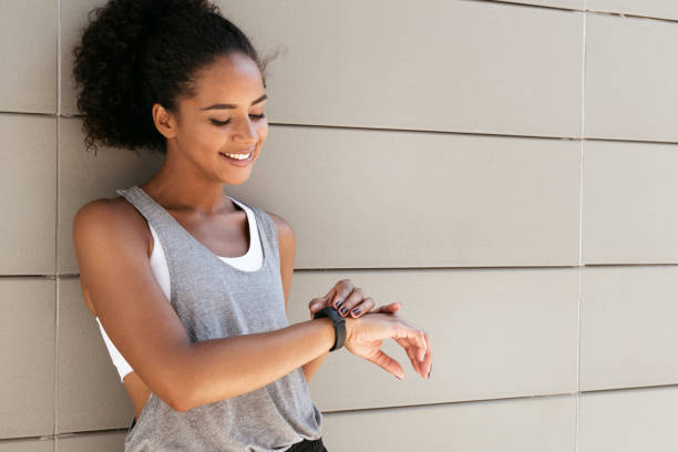 Fitness woman taking a break, checking activity tracker Fitness woman taking a break, checking activity tracker fitness tracker stock pictures, royalty-free photos & images