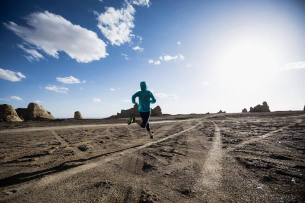 Fitness woman trail runner cross country running  on sand desert stock photo