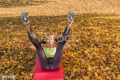 istock Fitness woman training outside in autumn park. Sport woman doing exercises during workout 863753546