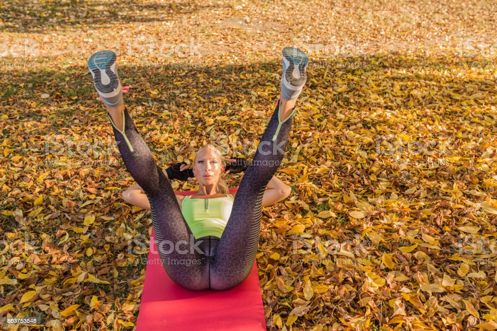 Fitness woman training outside in autumn park. Sport woman doing exercises during workout stock photo