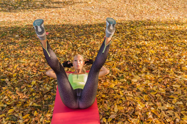 fitness woman training outside in autumn park. sport woman doing exercises during workout - yoga stock photos and pictures