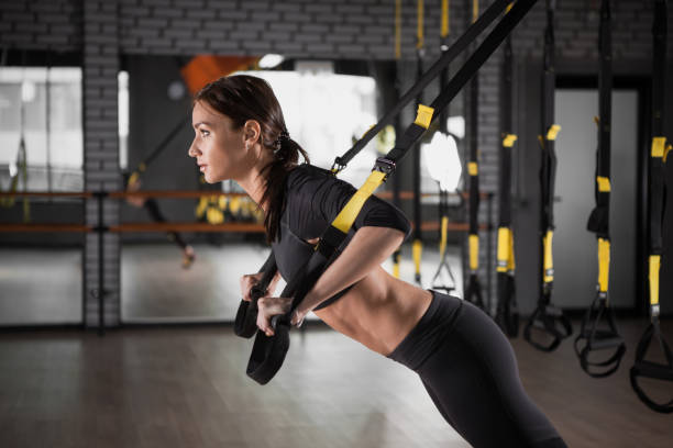 Fitness woman training with  fitness straps stock photo