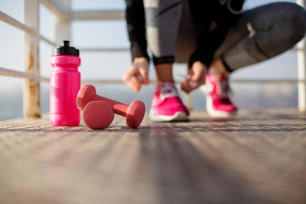 fitness-frau, die schnürsenkel zu binden - rosa training stock-fotos und bilder