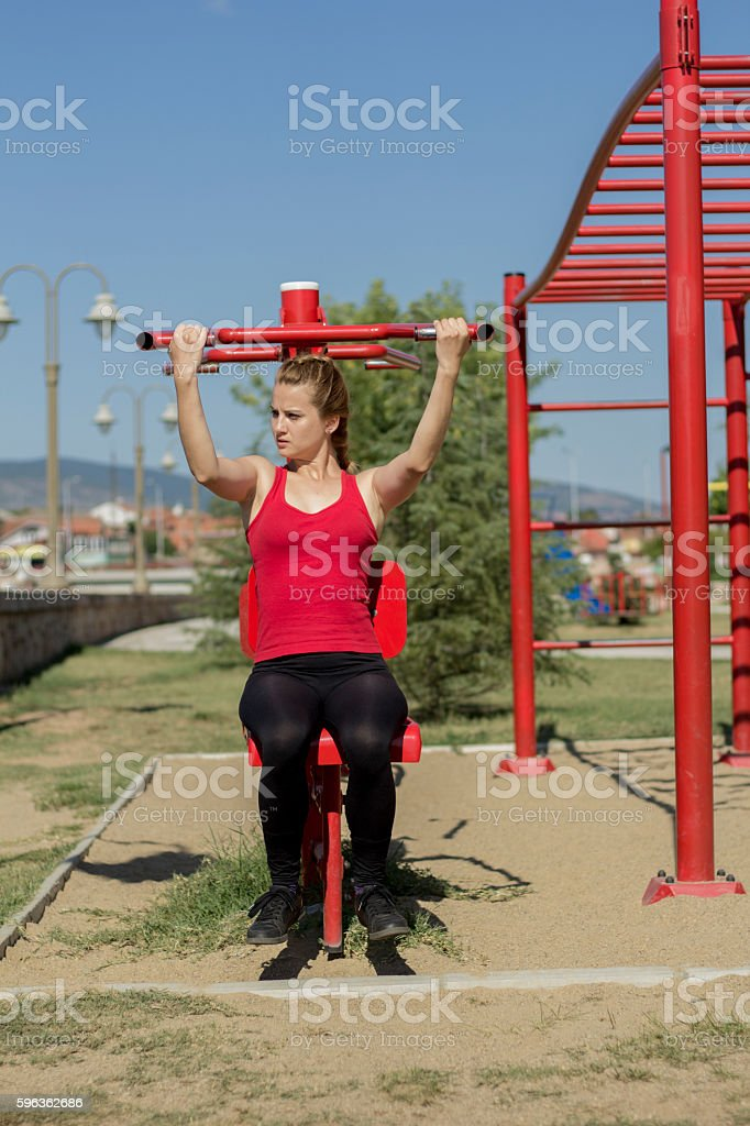 Fitness woman using equipment for fitness in the park royalty-free stock photo