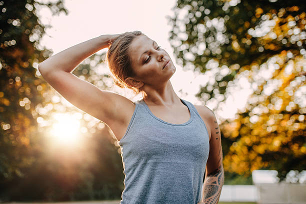 Fitness woman warming up in park Portrait of healthy young woman stretching her neck outdoors. Caucasian fitness model warming up in park. human neck stock pictures, royalty-free photos & images