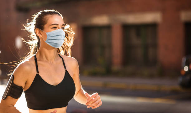 fitness woman wearing face mask during the lockdown stock photo