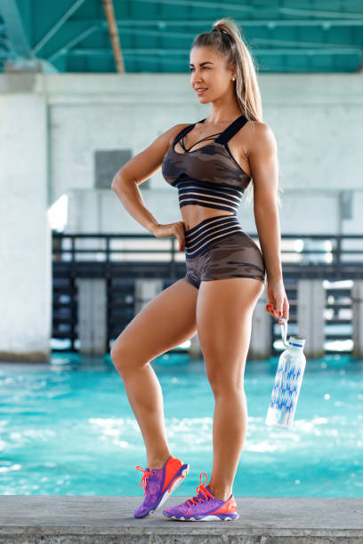 Fitness woman with a bottle of water outdoors. Active girl quenches thirst Fitness woman with a bottle of water outdoors. Active girl quenches thirst hot sexy butts stock pictures, royalty-free photos & images