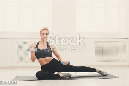 637596492istockphoto Fitness woman with dumbbells sitting on mat 905894312