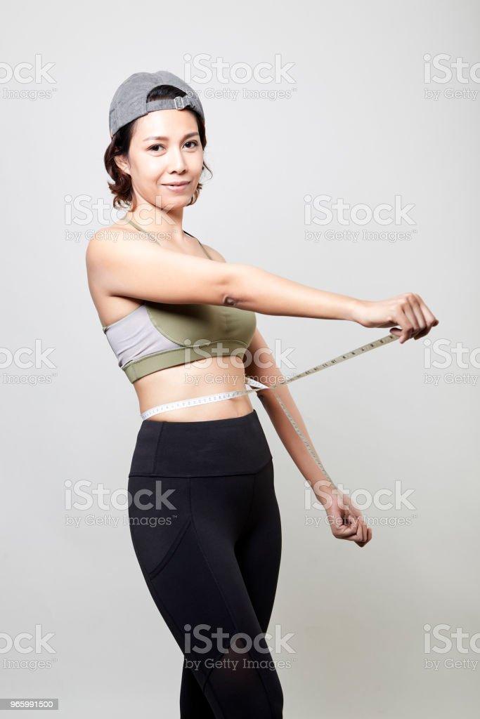 Fitness vrouw met maatregel tape op grijze achtergrond - Royalty-free Afvallen Stockfoto