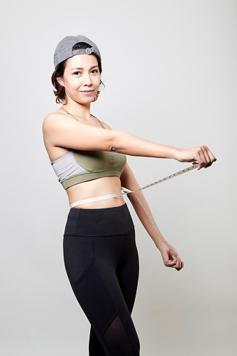 Fitness Vrouw Met Maatregel Tape Op Grijze Achtergrond Stockfoto en meer beelden van Afvallen