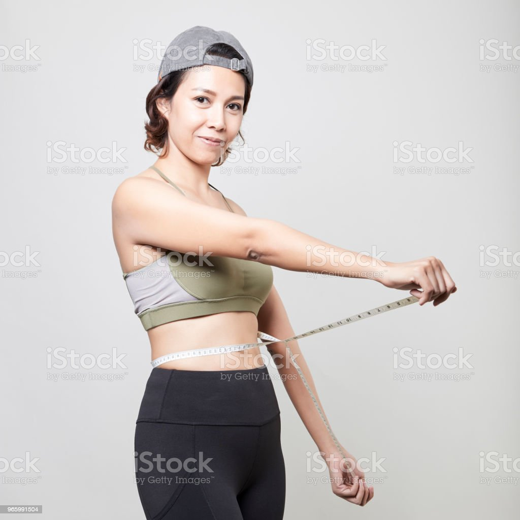 Fitness woman with measure tape on gray background - Royalty-free Abdomen Stock Photo