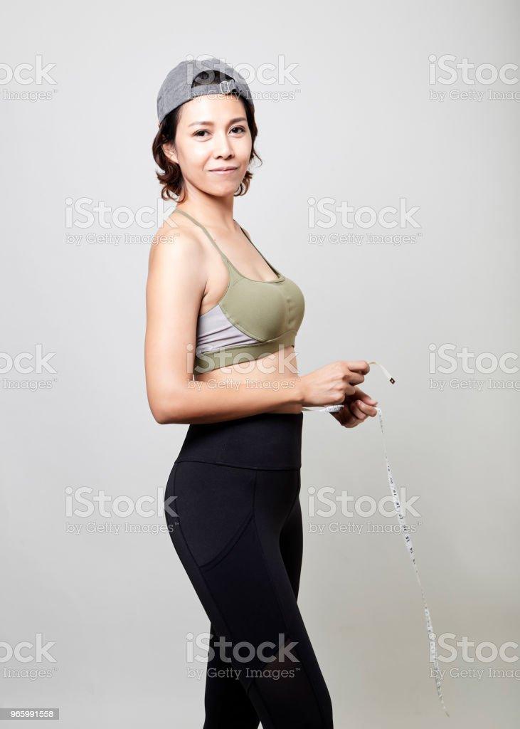 Fitness-Frau mit Maßband auf grauem Hintergrund - Lizenzfrei Abnehmen Stock-Foto
