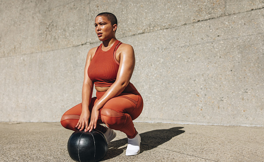 Fitness woman crouching with medicine ball on ground. Plus size female in sportswear with medicine ball looking away.
