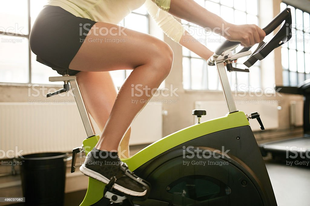 Fitness woman working out on exercise bike stock photo