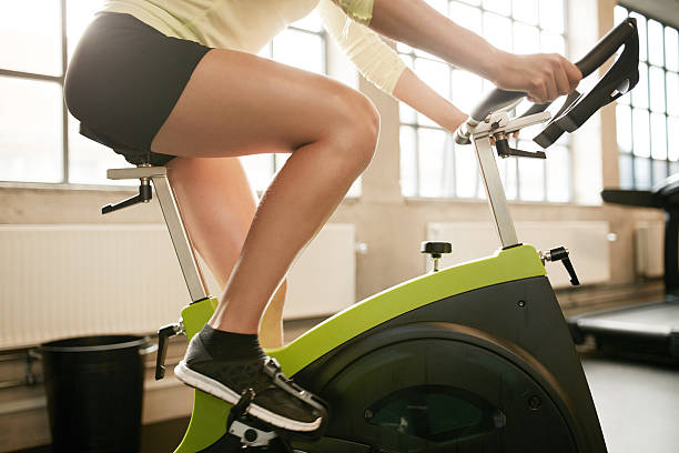 Fitness woman working out on exercise bike Cropped shot of fitness woman working out on exercise bike at the gym. Female exercising on bicycle in health club, focus on legs. exercise bike stock pictures, royalty-free photos & images