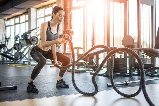 Fitness woman working out with battle rope at gym stock photo
