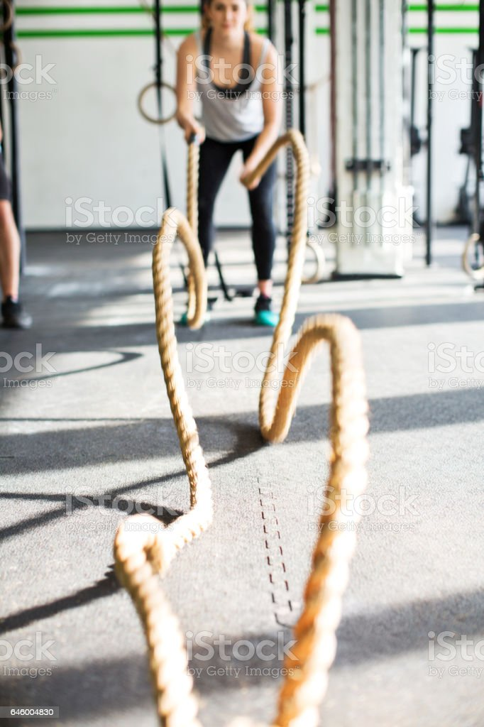 Fitness woman working out with battle ropes stock photo