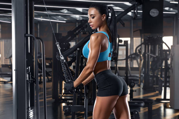 Fitness woman workout in gym. Sexy athletic girl doing exercise for triceps. Beautiful buttocks in thong stock photo
