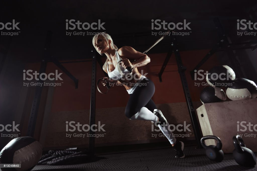 Fitness woman workout on the TRX in the gym stock photo