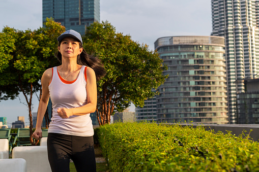 40 years old woman jogging in city park fog exercising series with singlet and leggings