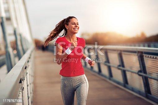 Beautiful fit woman in good shape jogging alone on city bridge.