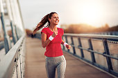 Beautiful fit woman in good shape jogging alone on city bridge.