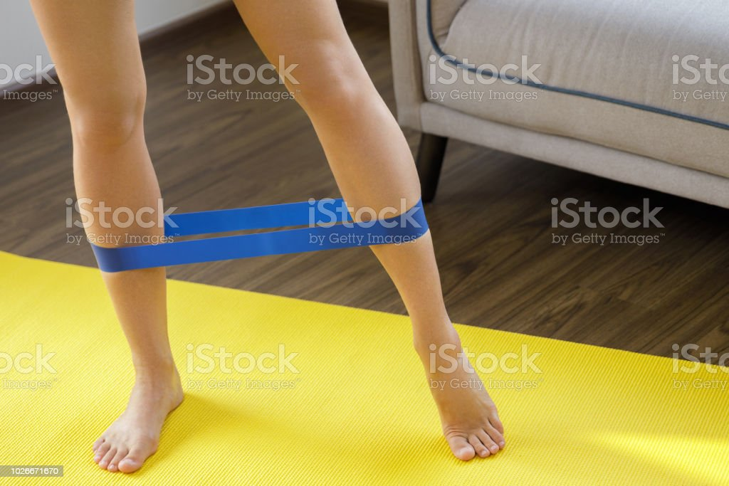 Woman during her fitness workout at home with rubber resistance band