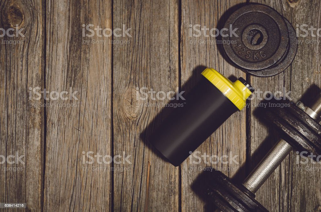 Fitness workout background. Dumbbells on wooden gym floor or table stock photo