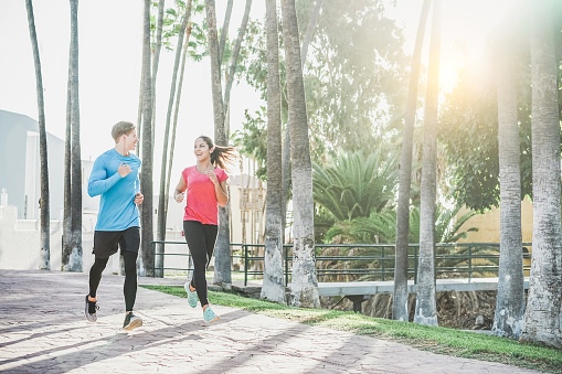 Fitness young couple running outdoor with palms in background - Sporty happy people training in tropical place - Healthy lifestyle, happiness, jogging and vitality concept - Warm filter