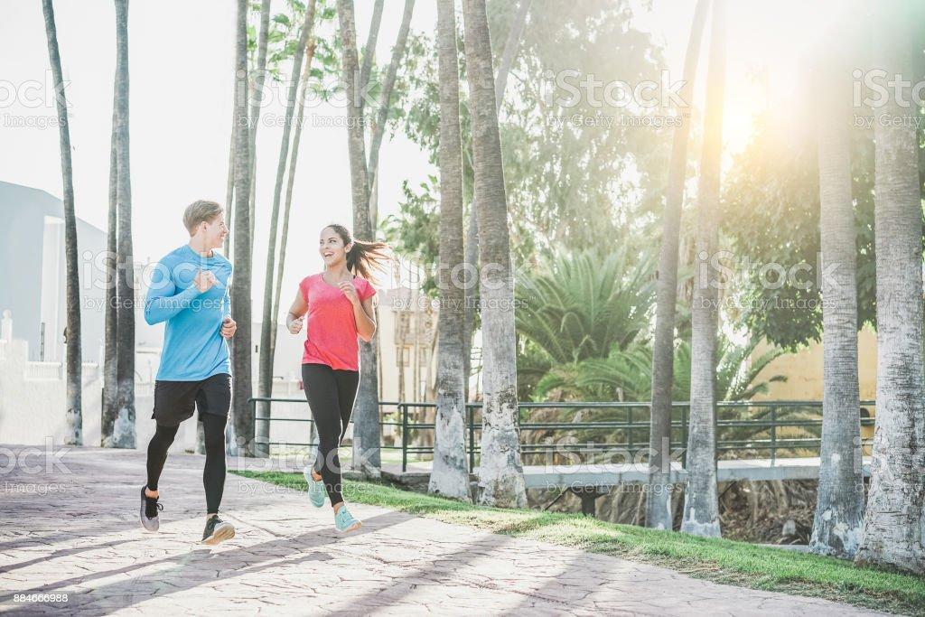 Junges Paar Fitness laufen im Freien mit Palmen im Hintergrund - sportliche glückliche Menschen in tropischen Ort training - gesunden Lebensstil, Glück, Joggen und Vitalität Konzept - warme filter – Foto