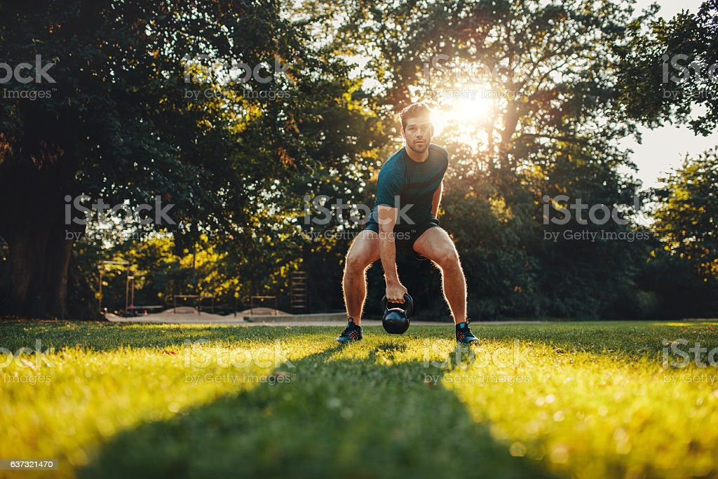 Fitness young man training with kettlebell in the park stock photo