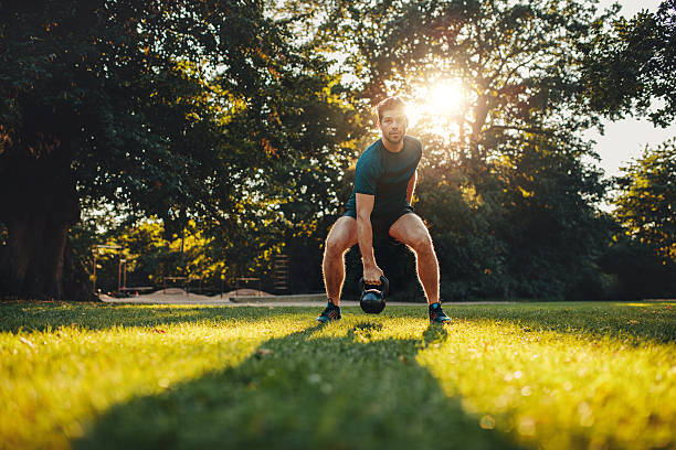 fitness young man training with kettlebell in the park - jacob ammentorp lund stock pictures, royalty-free photos & images