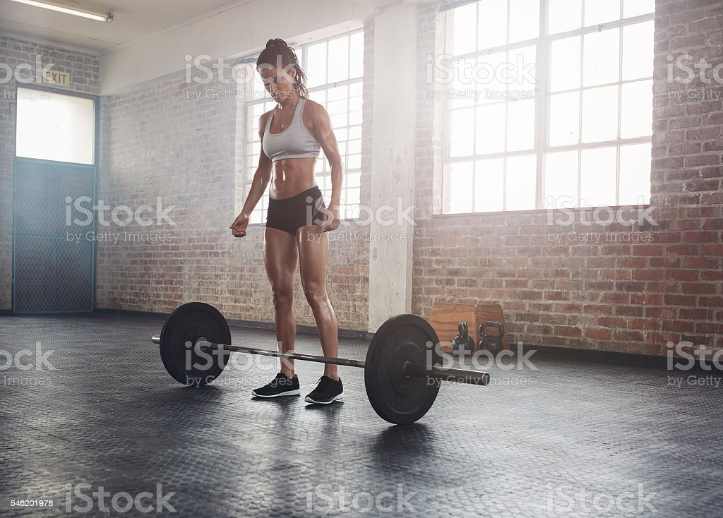 Fitness young woman at gym with barbell stock photo