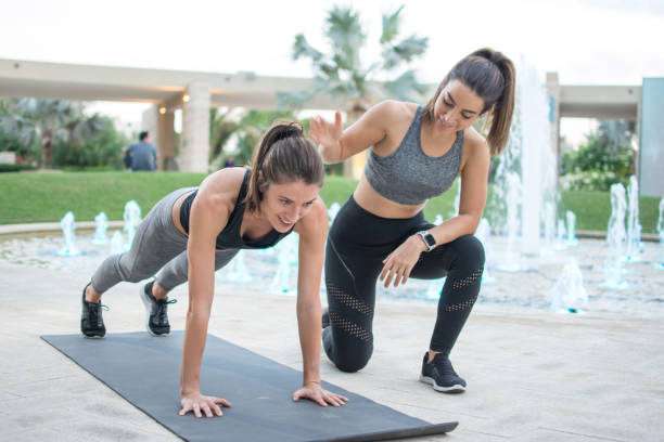 Fitness young woman doing push-ups with assistance of her female personal trainer outdoors stock photo