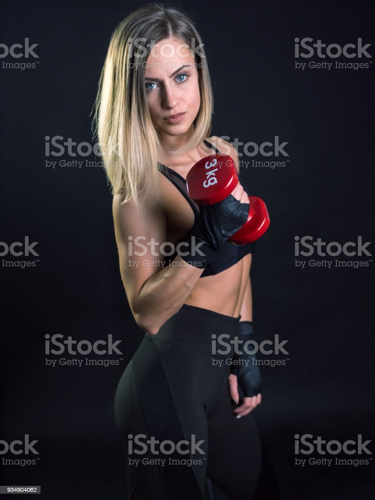 Fitness young woman model posing holding red dumbbell stock photo