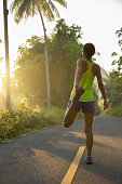 fitness young woman runner warming up before run on morning tropical forest trail