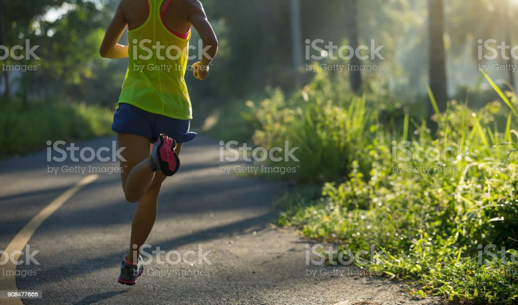 fitness young woman running on morning tropical forest trail – zdjęcie