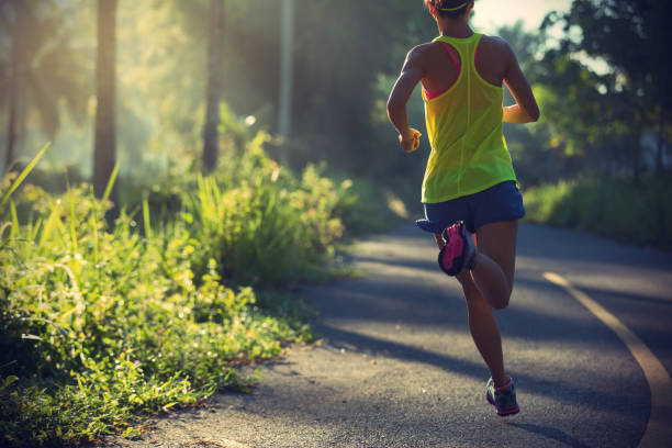 fitness young woman running on morning tropical forest trail stock photo