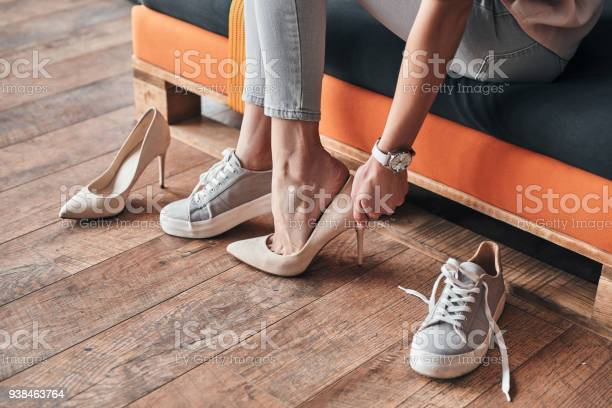 Close up of young woman trying on elegant shoes with high heels while sitting in the shoe store