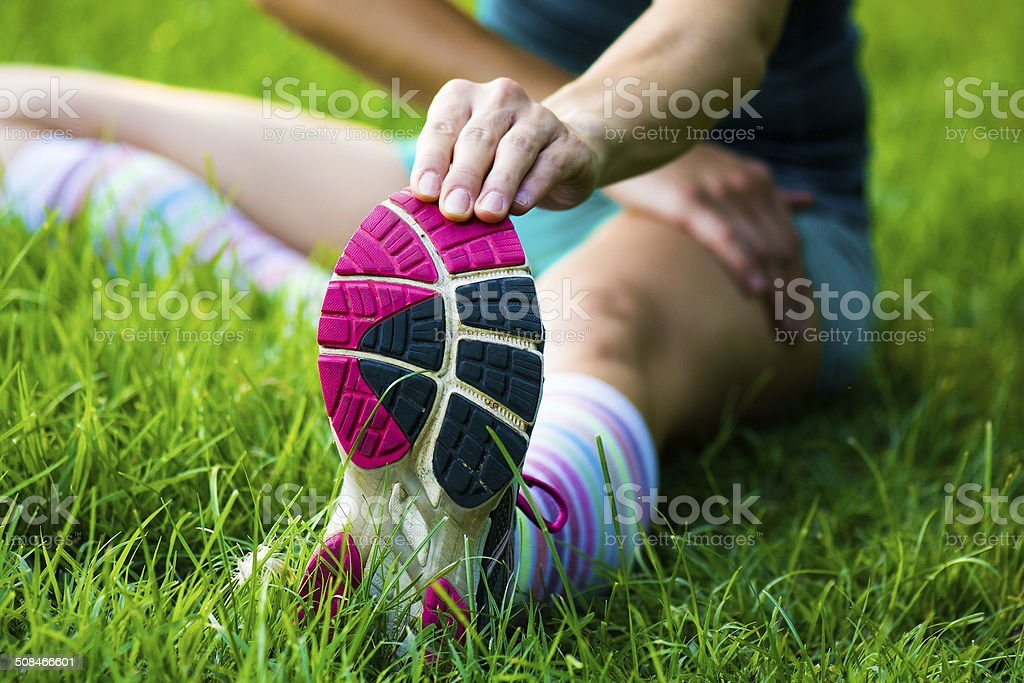 fitt girl getting streching her legs before running outdoors stock photo