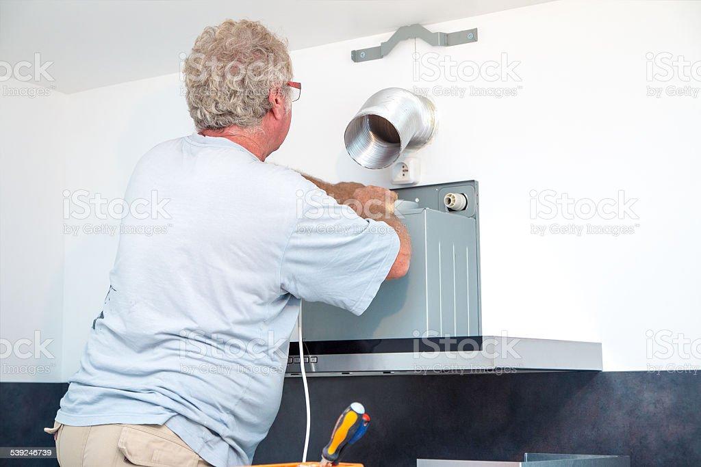 Fitter men installing range hood in new kitchen stock photo