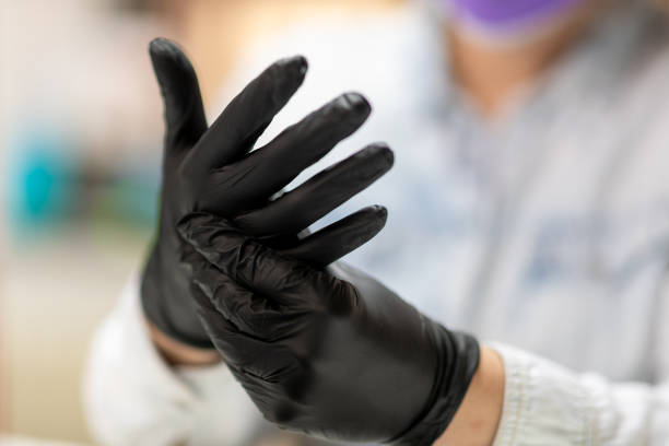 Fitting black protective gloves on hands stock photo