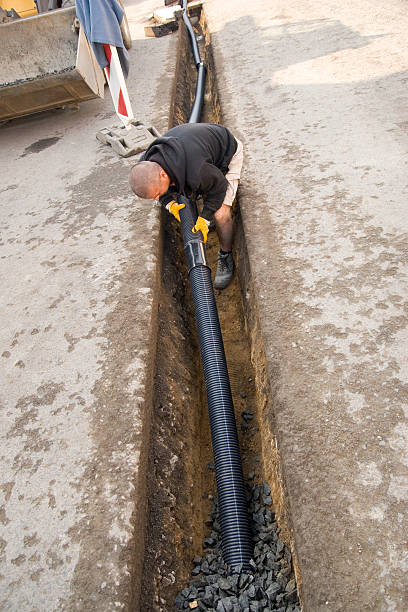 Fitting Drain Pipes Shot of a road worker in a long drainage ditch fitting drain pipes and connect the pipes to a sewer. pipefitter stock pictures, royalty-free photos & images