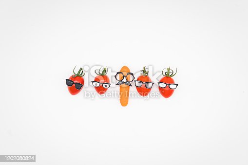 Group of anthropomorphic tomatoes and a baby carrot in disguise trying to fit in with the crowd. Fitting in vs standing out and group think vs individual styles