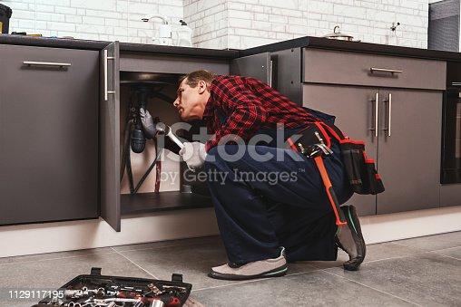 Fitting repair with wrench. Seniour handyman repairing washbasin at the kitchen