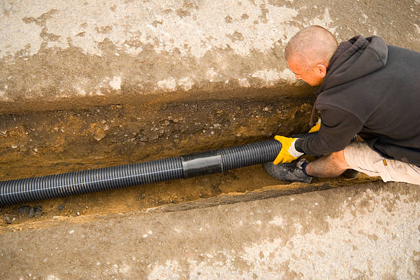 Fitting the Drain Pipes Shot of a road worker fitting drain pipes in a drainage ditch and connected the pipes to a sewer. Slight motion blur on the right end of the pipe pipefitter stock pictures, royalty-free photos & images